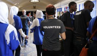 In this July 17, 2017, photo, the Afghanistan team, left, walks past two of the team members from Burundi, at right in black shirts, during the FIRST Global Robotics Challenge in Washington. Police tweeted missing person fliers Wednesday asking for help finding the teens, who had last been seen at the FIRST Global Challenge around the time of Tuesday's final matches. The missing team members include two 17-year-old girls and four males ranging in age from 16 to 18. (AP Photo/Jacquelyn Martin)