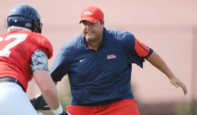 FILE - In this Aug. 10, 2015, file photo, Mississippi offensive line coach Matt Luke works on a drill with linemen during NCAA college football practice in Oxford, Miss. Mississippi coach Hugh Freeze has resigned after five seasons, bringing a stunning end to a once-promising tenure.The school confirmed Freeze's resignation in a release Thursday night, July 20, 2017. Luke has been named the interim coach. (Bruce Newman/The Oxford Eagle via AP, File)