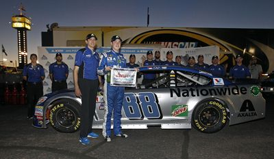 FILE - In this Nov. 11, 2016, file photo, Alex Bowman holds the pole flag with crew chief Greg Ives after winning the pole position for a NASCAR Sprint Cup series auto race at Phoenix International Raceway, in Avondale, Ariz. Dale Earnhardt Jr. got the replacement he wanted. Alex Bowman got his dream job. Hendrick Motorsports announced Thursday, July 20, 2017, that the 24-year-old Bowman will replace one of the series' biggest stars in the No. 88 car next season after Earnhardt retires. (AP Photo/Ralph Freso, File)