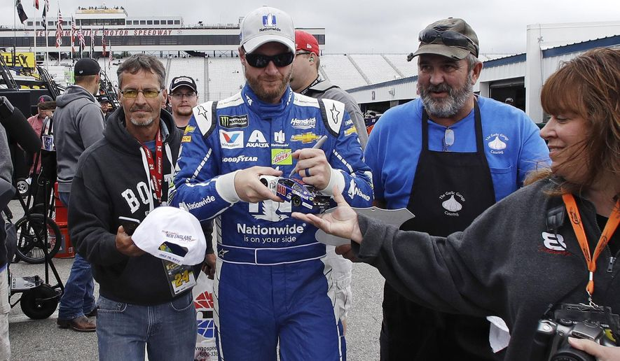 Driver Dale Earnhardt Jr. signs autographs for fans as he walks through the garage area after a NASCAR auto racing practice at the New Hampshire Motor Speedway in Loudon, N.H., Friday, July 14, 2017. (AP Photo/Charles Krupa)