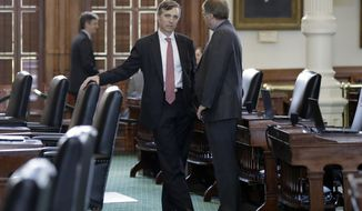 Texas Sen. Van Taylor, R-Plano, left, talks with Sen. Brian Birdwell, R-Granbury, right, on the second day of a special session ordered by Republican Gov. Greg Abbott, in Austin, Texas, Wednesday, July 19, 2017. Conservatives in the state Senate are swiftly advancing sunset legislation, a regulatory bill that must pass before the legislature can work on anti-abortion measures, school vouchers and defanging local ordinances in Texas' big and liberal cities. (AP Photo/Eric Gay)