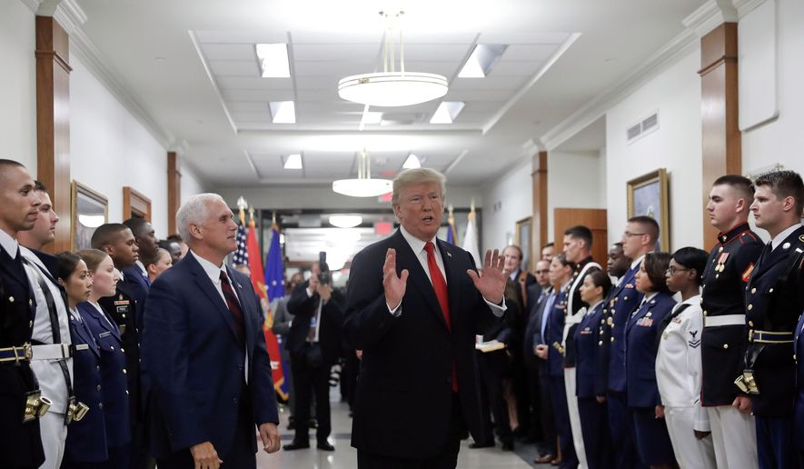 President Donald Trump stops to answer a reporter's question after greeting military personnel during a visit to the Pentagon, Thursday, July 20, 2017. Watching is Vice President Mike Pence. (AP Photo/Pablo Martinez Monsivais)