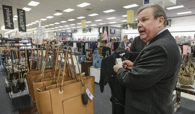 In this May 24, 2017, photo, Tom Shull, CEO of the Army & Air Force Exchange Service, checks a price tag at a store inside the Exchange, at Offutt Air Force Base, Neb. Starting in fall 2017, all honorably discharged veterans will be eligible to shop tax-free online at the Exchange with the same discounts they enjoyed at stores on base while they were in the military. It's the latest way in which the Army & Air Force Exchange Service is trying to keep its customers as the armed forces shrink and airmen and soldiers buy more for delivery. (AP Photo/Nati Harnik)
