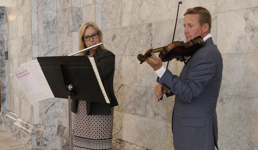 Republican Reps. Mary Dye and Vincent Buys play music in the Capitol Rotunda on the last day of the third special session, Thursday, July 20, 2017, in Olympia, Wash. Lawmakers have been in session for more than 190 days this year as they've struggled to reach agreement on several issues. (AP Photo/Rachel La Corte)