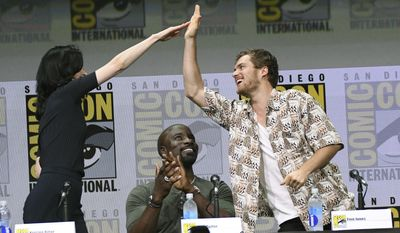 "Krysten Ritter, left, and Finn Jones, right, high five each other as Mike Colter looks on at the ""Marvel's The Defenders"" panel on day two of Comic-Con International on Friday, July 21, 2017, in San Diego, Calif. (Photo by Al Powers/Invision/AP)"
