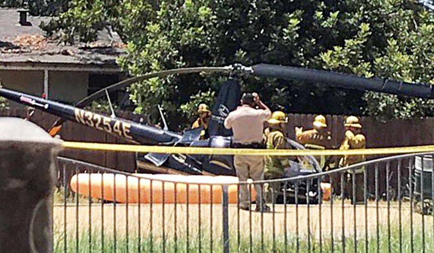 A Robinson R44 helicopter is seen where it crash-landed on a street in the Sherman Oaks neighborhood of Los Angeles' San Fernando Valley Friday afternoon, July 21, 2017. Four people who were on board appeared to have non-life-threatening injuries, fire officials reported. The aircraft did not catch fire, and nobody on the ground was hurt. (Zelneisha Fields via AP)