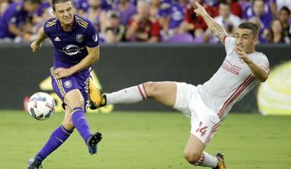 Orlando City's Will Johnson, left, takes a shot on goal as Atlanta United's Carlos Carmona (14) comes in to defend during the first half of an MLS soccer match, Friday, July 21, 2017, in Orlando, Fla. (AP Photo/John Raoux)
