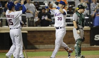 Oakland Athletics catcher Josh Phegley, right, reacts as New York Mets' Michael Conforto (30) celebrates with Matt Reynolds (15) after hitting a two-run home run during the seventh inning of an interleague baseball game Friday, July 21, 2017, in New York. (AP Photo/Frank Franklin II)