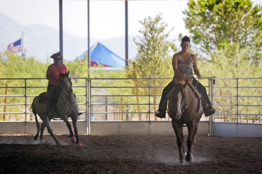 ADVANCE FOR THE WEEKEND OF JULY 22-23 AND THEREAFTER - In a Sunday July 2, 2017 photo, Gina Bell, right, gets a feel for Callie, a 15-year-old horse that is up for adoption, at the Lone Mountain Equestrian arena in Las Vegas.  Local Equine Assistance Network is a nonprofit that helps horses that have been abandoned or neglected. (Steve Marcus/Las Vegas Sun via AP)