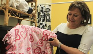 New Mexico Gov. Susana Martinez holds up one of the many blankets made by a volunteer for children who will be coming through a new receiving center operated by social workers, during a tour with the state Children, Youth and Families Department in Albuquerque, N.M., Friday, July 21, 2017. As a former prosecutor, the two-term Republican governor said children who are taken into state protective custody following trouble within their homes need a safe place where they can feel comfortable while social workers and other authorities sort out their cases or work to find foster families. (AP Photo/Susan Montoya Bryan)