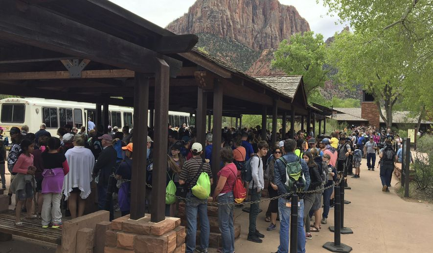 In this Nov. 2016, photo provided by Zion National Park, people line up at Zion National Park, in Utah. The sweeping red-rock vistas at Zion National Park are increasingly filled with a bumper crop of visitors, and now park managers are weighing an unusual step to stem the tide: : Requiring tourists to make RSVPs to get in.  (Zion National Park via AP)