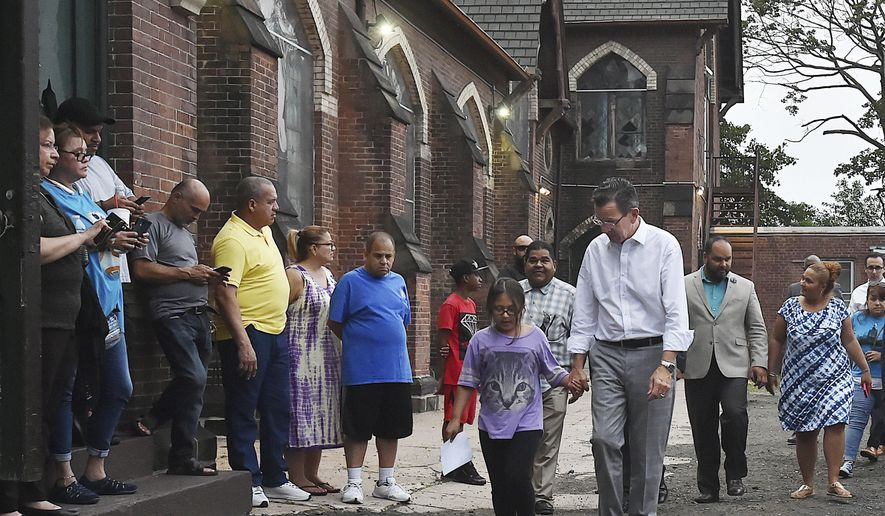 """In this Thursday, July 20, 2017 photo, Connecticut Gov. Dannel P. Malloy walks with nine-year-old Hayley Chavarria before speaking at a press conference at Iglesia de Dios Pentecostal Church in New Haven where  her mother Nury Chavarria, who was supposed to be deported Thursday to Guatemala, has taken sanctuary. Malloy, said the attempt to deport the housekeeper and mother of four shows President Donald Trump's administration is not being truthful when it says its immigration policies are focused on """"the bad guys."""" (Catherine Avalone/New Haven Register via AP)"""