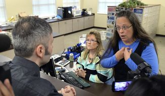 In this Sept. 1, 2015, file photo, Rowan County Clerk Kim Davis, right, talks with David Moore following her office's refusal to issue marriage licenses at the Rowan County Courthouse in Morehead, Ky. On Friday, July 21, 2017, a federal judge has ordered Kentucky taxpayers to pay more than $220,000 in attorneys' fees for the elected county clerk who caused a national uproar by refusing to issue marriage licenses to same-sex couples. (AP Photo/Timothy D. Easley, File)