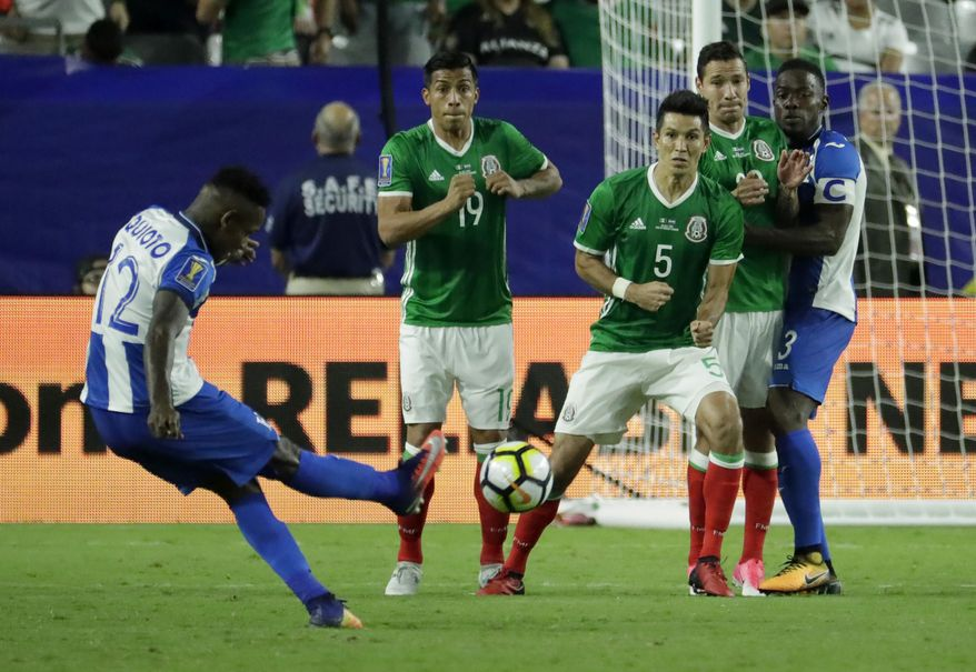 Honduras' Romell Quioto, left, strikes the ball during a free kick against Mexico's Angel Sepulveda (19) and Jesus Molina (5) during a CONCACAF Gold Cup quarterfinal soccer match, Thursday, July 20, 2017, in Glendale, Ariz. (AP Photo/Matt York)