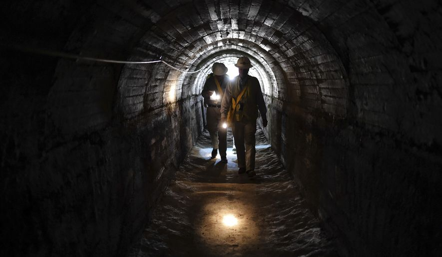 In this Wednesday, July 19, 2017 photo, Michael Grahek, of Los Angeles Department of Water and Power, walks in the Maclay Highline tunnel that is being reconnected to the aqueduct in Sylmar, in Los Angeles. The tunnel is part of the Maclay Highline system of channels and tunnels that supplied water to homes and farms in Sylmar and the Sunland-Tujunga area. Los Angeles is restoring the century-old water tunnel to capture runoff from the Sierra Nevada, which had a record snowfall this winter after years of drought. (Hans Gutknecht/Los Angeles Daily News via AP)