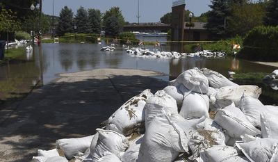 Sandbags arev ready to be deployed on La Fox River Drive in Algonquin, Ill., Thursday, July 20, 2017. Flood levels along two northern Illinois rivers looked to be falling after flooding this week but another round of rain has them rising again.  (Rick West /Daily Herald via AP)