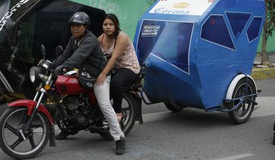 A motorcycle taxi driver pauses to look at marines blocking the area where a suspected drug gang leader and seven others were killed in a shootout in the Tlahuac district of Mexico City, Thursday, July 20, 2017. Mexico City residents were stunned by the sight of drug-war-style violence, including burnt-out vehicles and road blockades by gang-sympathizing motorcycle taxi drivers, in the nation's capital, sights that had previously been seen only in violence-wracked cities like Reynosa and Nuevo Laredo.(AP Photo/Rebecca Blackwell)