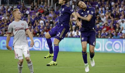 Orlando City's Jonathan Spector (2) and Jose Aja (4) try to head the ball to the goal in front of Atlanta United's Jeff Larentowicz (18) on a corner kick during the first half of an MLS soccer match, Friday, July 21, 2017, in Orlando, Fla. (AP Photo/John Raoux)