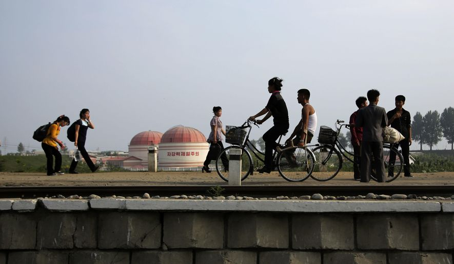 "North Koreans walk while some cycle past a factory dome with Korean words painted on its side which read ""First priority: self development"" at the end of a work day on Thursday, July 20, 2017, in Hamhung, North Korea. Hamhung is North Korea's second largest city. (AP Photo/Wong Maye-E)"