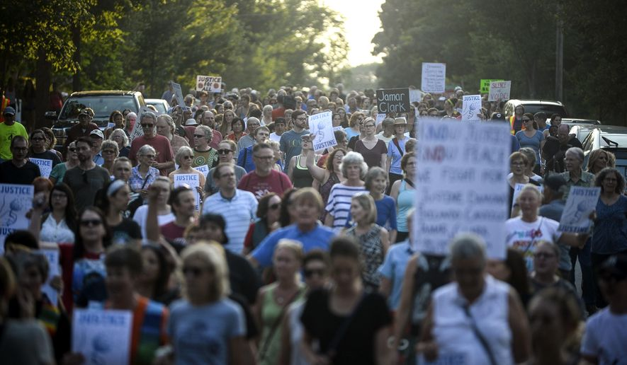 Hundreds march from the site of Justine Damond's shooting to Beard's Plaissance Park during a march in honor of Damond Thursday, July 20, 2017, in Minneapolis. Damond, of Australia, was shot and killed by a Minneapolis police officer on Saturday, July 15 after calling 911 to report what she believed was a possible assault. (Aaron Lavinsky /Star Tribune via AP)