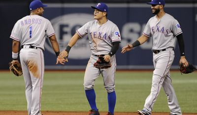 Texas Rangers' Elvis Andrus, Shin-Soo Choo, and Nomar Mazara celebrate a win over the Tampa Bay Rays in 10 innings of a baseball game Friday, July 21, 2017, in St. Petersburg, Fla. (AP Photo/Steve Nesius)