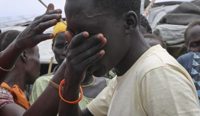 In this photo taken Friday, May 26, 2017, former child soldier James cries uncontrollably as he is reunited with his mother for the first time in 3 years, while family and friends brush their hands over his face in a Nuer tradition that wishes him a long life, at a protection of civilians site in Bentiu, South Sudan. James, one of an estimated 18,000 children fighting in South Sudan according to the United Nations, was left for dead on a battlefield while back home his mother mourned him and held a funeral without a body, having no idea that he was still alive. (AP Photo/Sam Mednick)
