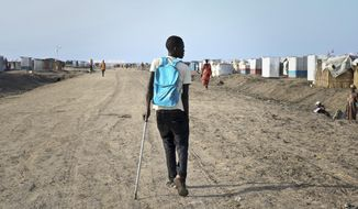 In this photo taken Monday, May 29, 2017, former child soldier James walks down the road from his small hut in a protection of civilians site to his first day at his new school, after recently being reunited with his mother who had thought he was dead, in Bentiu, South Sudan. James, one of an estimated 18,000 children fighting in South Sudan according to the United Nations, was left for dead on a battlefield while back home his mother mourned him and held a funeral without a body, having no idea that he was still alive. (AP Photo/Sam Mednick)