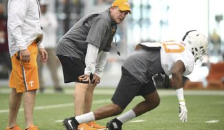 FILE - In this March 31, 2016, file photo, Tennessee defensive coordinator Bob Shoop, center, coaches a player during spring football practice at Anderson Training Center  in Knoxville, Tenn. Shoop has encountered plenty of adversity since coming over from Penn State last year. His defense was decimated by injuries and struggled to slow down anyone late last season. Now that he's getting ready to begin his second season with the Volunteers, his former employer has sued him for breach of contract. (Adam Lau/Knoxville News Sentinel via AP, File)