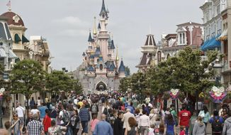 FILE - In this May 12, 2015, file photo, visitors walk near Sleeping Beauty's Castle at Disneyland Paris, in Marne la Vallee, east of Paris. Walt Disney Parks and Resorts announced new attractions for international and domestic Disney parks during its D23 fan expo in Anaheim, Calif., on July 15. Most of the upcoming projects are expected to be completed by Disney World's 50th anniversary in 2021. (AP Photo/Michel Euler, File)