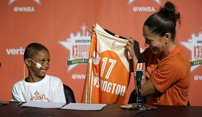 "Seattle Storm guard Sue Bird, right, holds up a jersey for Eniyah Washington, 6, after Bird signed the youngster to a WNBA All-Star basketball ""contract"" for the Western Conference team, through the Austen Everett Foundation, Friday, July 21, 2017, in Seattle. Eniyah, also known as Niyah, is herself a basketball player who was diagnosed last year with Acute Lymphoblast Leukemia and is being treated with an intensive chemotherapy process. Bird will represent the Western Conference in Saturday's WNBA All-Star game. (AP Photo/Elaine Thompson)"