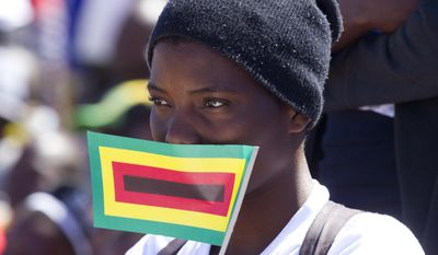 A supporter of Zimbabwe President Robert Mugabe listens to his speech at a rally in Lupane about 170 Kilometres north of Bulawayo, Friday, July, 21, 2017. Mugabe's rally is his first since his return from a routine medical review in Singapore. The world's oldest leader has launched a series of rallies targeting the youth ahead of Presidential elections set for 2018. (AP Photo/Tsvangirayi Mukwazhi)