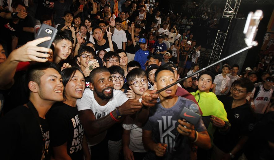NBA Cleveland Cavaliers guard Kyrie Irving takes photos with fans while he holds a short basketball clinic with young Taiwanese players in Taipei, Taiwan, Saturday, July 22, 2017.(AP Photo/Chiang Ying-ying)
