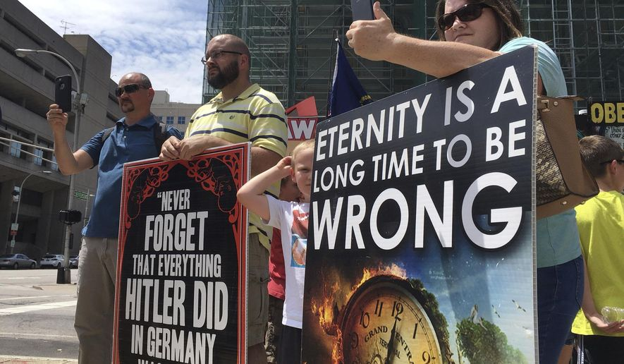 """In this Wednesday, July 19, 2017, photo abortion opponents with a group called Operation Save America gather during a rally in downtown Louisville, Ky.  A federal judge issued an order Friday, July 21, 2017, to keep protesters away from a """"buffer zone"""" outside Kentucky's only abortion clinic, which is targeted by a national anti-abortion group.  U.S. District Judge David J. Hale issued a temporary restraining order sought by federal prosecutors in a pre-emptive move ahead of vigils by Operation Save America. The order is aimed at preventing abortion foes from impeding access to EMW Women's Surgical Center in Louisville. (AP Photo/Dylan Lovan) **FILE**"""
