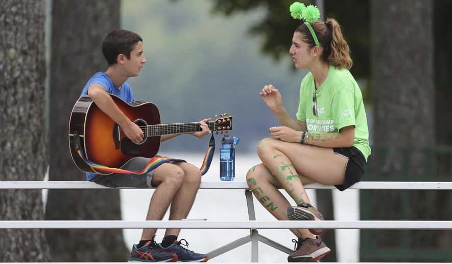 A camper from Israel, left, and the United Kingdom discuss music at the Seeds of Peace camp, Thursday, July 20, 2017, in Otisfield, Maine. For 25 years, Israeli and Palestinian teens have been coming to the woods of Maine, along with campers from other countries at conflict, to try to work toward peace. They're no closer to resolving the conflict but there's still hope, the latest group says. (AP Photo/Robert F. Bukaty)