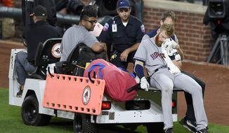 Houston Astros' Colin Moran holds a towel as he is carted off the field after he sustained an injury to his face during his at bat in the sixth inning of a baseball game against the Baltimore Orioles, Saturday, July 22, 2017, in Baltimore. (AP Photo/Nick Wass)