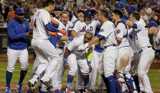 New York Mets' Wilmer Flores, bottom center, is greeted by teammates at home plate after hitting a walk-off solo home run during the ninth inning of a baseball game to defeat the Oakland Athletics, Saturday, July 22, 2017, in New York. (AP Photo/Julie Jacobson)