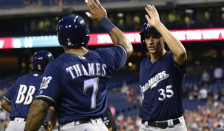 Milwaukee Brewers' Brent Suter, right, high-fives Eric Thames (7) after scoring on a Ryan Braun double during the third inning of a baseball game against the Philadelphia Phillies, Saturday, July 22, 2017, in Philadelphia. (AP Photo/Derik Hamilton)