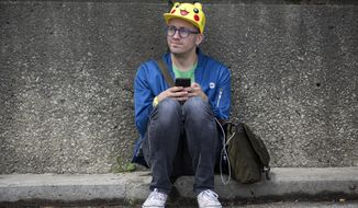 Ryan Copple of Los Angeles sits in the shade as he struggles to play Pokemon Go at the Pokemon Go Fest Saturday, July 22, 2017, at Grant Park in Chicago. Many festival attendees had trouble getting the augmented-reality cellphone game to work. By the afternoon, Mike Quigley, chief marketing officer of the game's developer, Niantic, announced all ticket holders would receive refunds and be issued $100 in credits for use in the app. Copple came to Chicago from Los Angeles just for the event. (Erin Hooley/Chicago Tribune via AP)