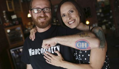 ADVANCE FOR USE SATURDAY, JULY 22 - In this Wednesday, July 12, 2017, Casey Carr, and his wife Heidi, show off Casey's tattoo of his and his wife's initials on his arm, which match the letters of the C and H Sugar Company, at the Lost Canvas Coffee Shop in Keokuk, Iowa. As a result of social media attention garnered by the tattoo the couple is set to receive a year's worth of products from C&H Sugar. (John Lovretta/The Hawk Eye via AP)