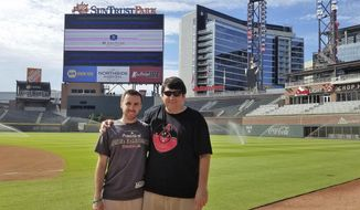 In this 2017 photo provided by Frank Gennario Jr., Frank Gennario Jr. and his son, Tony, pose at SunTrust Park in Atlanta.  Frank Gennario lost his father to bone cancer when he was 16, and he clings tightly to memories of their days at Yankee Stadium. When Frank's only son was nearing the same age, it became critical to him that they build those same ballpark memories. So the pair set a goal: see their beloved Arizona Diamondbacks play in every big league park. Ten years later, they have completed their quest. (Frank Gennario Jr. via AP)