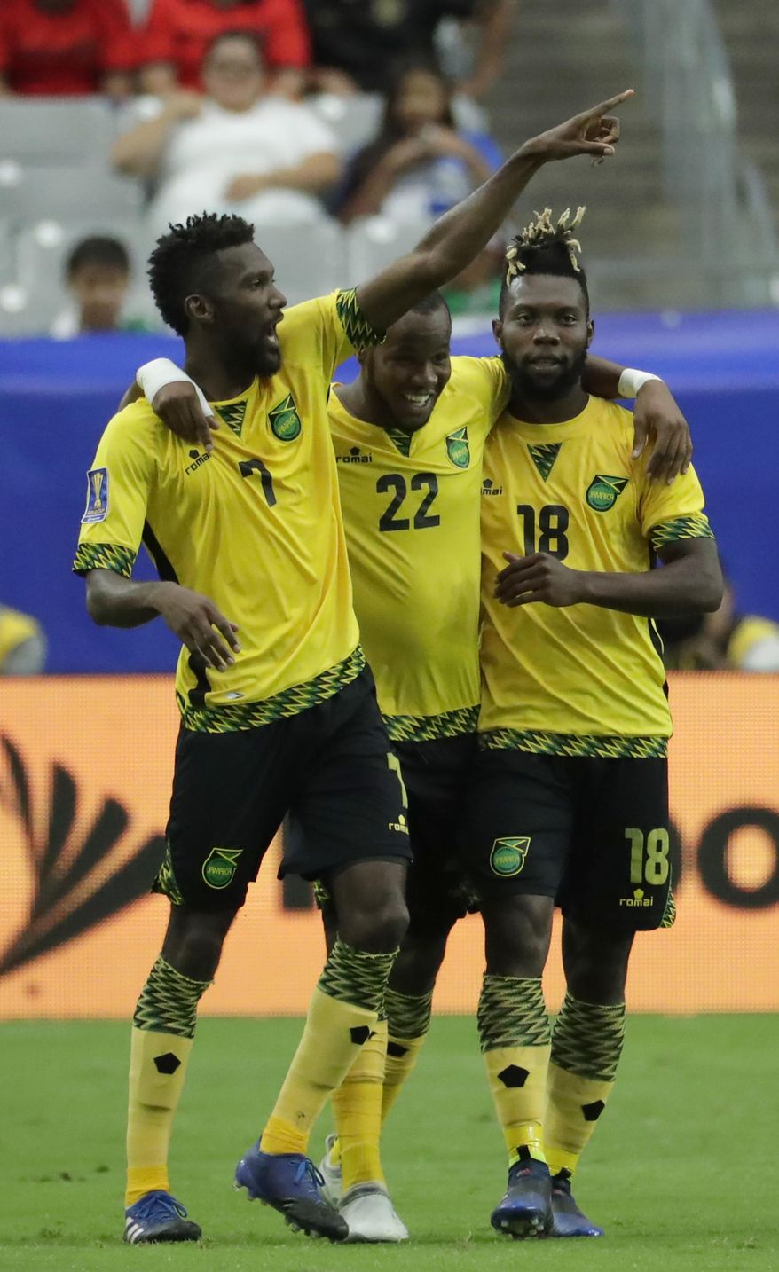 Jamaica's Romario Williams (22) celebrates with teammates Shaun Francis (7) and Owayne Gordon (18) after Williams scored his team's second goal against Canada during a CONCACAF Gold Cup quarterfinal soccer match, Thursday, July 20, 2017, in Glendale, Ariz. (AP Photo/Matt York)