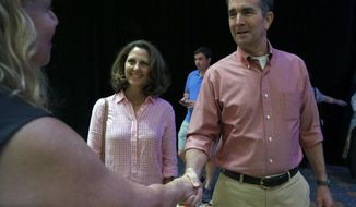 Democratic gubernatorial candidate Lt. Gov. Ralph Northam, right, and his wife Pam, center, are greeted by Virginia Bar Association Executive Director Yvonne C. McGhee, left, at the Omni Homestead Resort in Hot Springs, Va., Saturday, July 22, 2017 where Northam will debate withGOP gubernatorial candidate Ed Gillespie at the Virginia Bar Association meeting.   (Bob Brown/Richmond Times-Dispatch via AP)