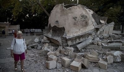 A tourist walks past a damaged structure outside a mosque after an earthquake at the Greek island of Kos on Saturday, July 22, 2017. Hundreds of people on the eastern Greek island of Kos have spent the night sleeping outdoors after a powerful Friday earthquake killed two tourists and injured nearly 500 others across the Aegean Sea region in Greece and Turkey.(AP Photo/Petros Giannakouris)