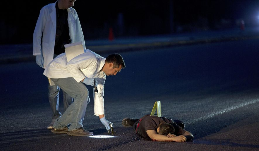 FILE - In this early Thursday, June 29, 2017 file photo, investigators mark the spot where spent bullet casings fell next to a body lying on a road in the town of Navolato, Sinaloa state, Mexico. Fifty-nine AK type and AR-15 casings were found in the area. (AP Photo/Enric Marti, File)