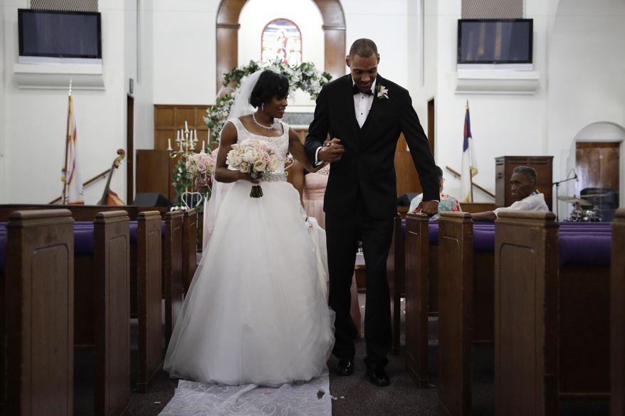 Two-time Olympic jumper Jamie Nieto, right, who was paralyzed from neck down 15 months ago after a spinal cord injury, pauses for a moment while walking down the aisle with his bride Shevon Stoddart after their wedding ceremony Saturday, July 22, 2017, in El Cajon, Calif. Step by halting step, Nieto made good on his vow to walk his new wife down the aisle of the church and out the door to a waiting limousine. (AP Photo/Jae C. Hong)
