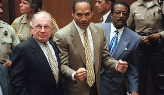 FILE--In this Oct. 3, 1995 file photo, O.J. Simpson reacts as he is found not guilty of murdering his ex-wife Nicole Brown Simpson and her friend Ron Goldman, at the Criminal Courts Building in Los Angeles. For an earlier generation, OJ Simpson was a symbol of racial tension and uneven justice.  While the issues around race and policing remain today, Simpson's racial symbolism is largely seen as a relic. At left is defense lawyer F. Lee Bailey and at right is defense attorney Johnnie Cochran Jr. Defense attorney Robert Shapiro is in profile behind them. (AP Photo/Daily News, Myung J. Chun, Pool, File)