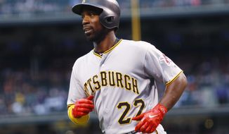 Pittsburgh Pirates' Andrew McCutchen smiles after scoring on an infield single by David Freese off Colorado Rockies starting pitcher Jeff Hoffman in the first inning of a baseball game Friday, July 21, 2017, in Denver. (AP Photo/David Zalubowski)