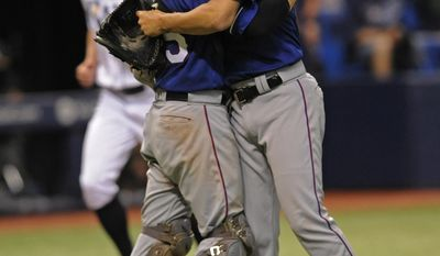 Texas Rangers catcher Jonathan Lucroy, left, and reliever Alex Claudio celebrate a win over the Tampa Bay Rays after a baseball game Saturday, July 22, 2017, in St. Petersburg, Fla. (AP Photo/Steve Nesius)