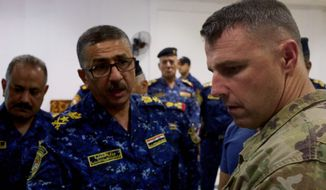 Lieutenant General Raid Shaker Jawlat, center, of the Iraqi federal police talks with Colonel Pat Work of the U.S. Army's 82nd airborne division as they look at a map of Mosul, in Mosul, Iraq, Friday, June 30, 2017. Work warned that as Iraqi forces close in on the Islamic State group's last remaining positions in Mosul the troops are at increased risk of friendly fire attacks. (AP Photo/Balint Szlanko)