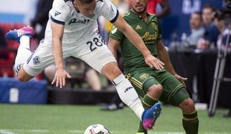 Vancouver Whitecaps defender Jake Nerwinski (28) vies for control of the ball with Portland Timbers midfielder Sebastian Blanco, right, during the first half of MLS soccer game action in Vancouver, British Columbia, Sunday, July, 23, 2017. (Jonathan Hayward/The Canadian Press via AP)